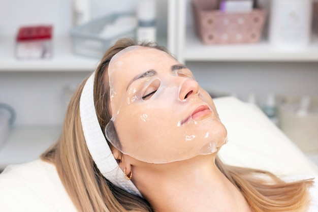 Young woman uses a hydrogel mask on her face.