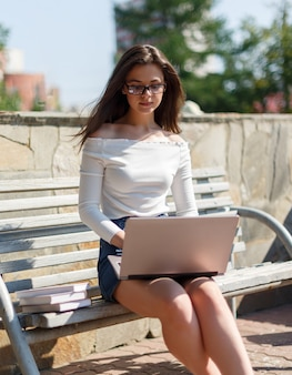 Young woman uses laptop sitting on a park bench.