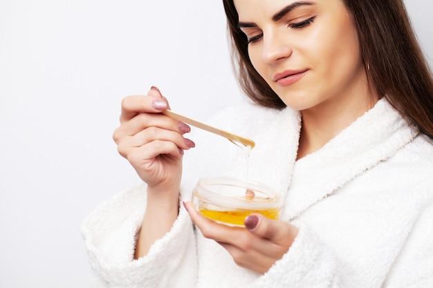 Молодая женщина удаляет волосы жидким воском.
