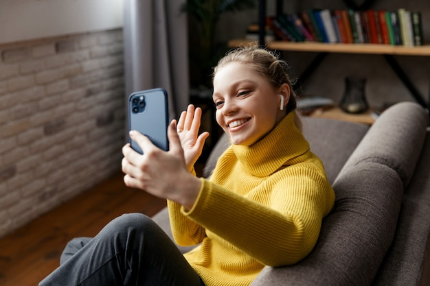 Молодая женщина использует телефон для видеозвонка со своими друзьями. фото высокого качества