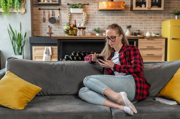 若い女性が自宅のソファに座ってスマートフォンを使用