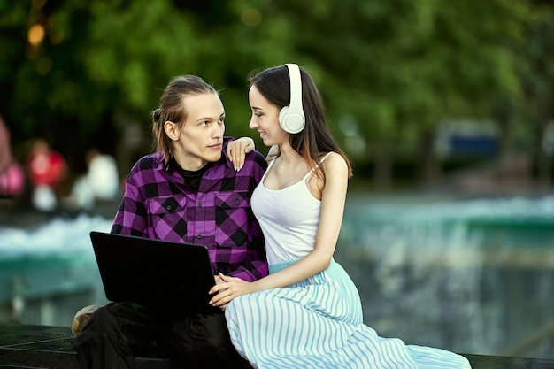 Молодая женщина использует беспроводные наушники, чтобы слушать музыку, которую ее парень выбирает онлайн на ноутбуке