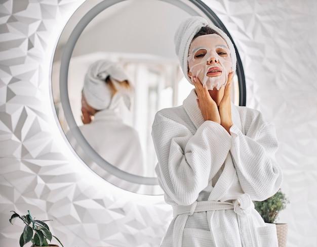 Молодая женщина, используя косметическую маску для лица