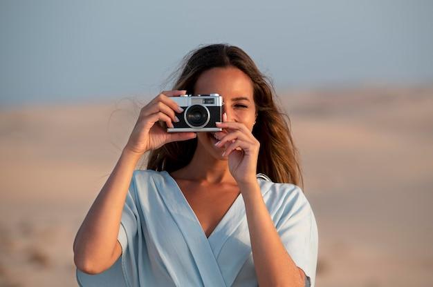 彼女の休暇でカメラを使用して若い女性