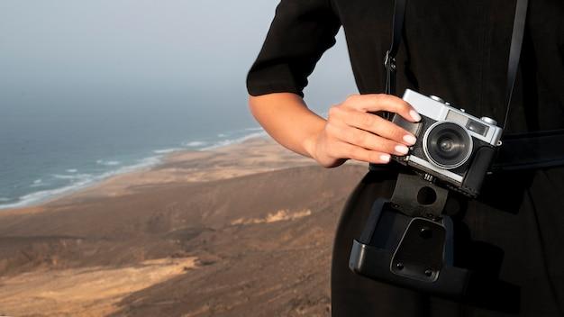 그녀의 휴가에 카메라를 사용하는 젊은 여자