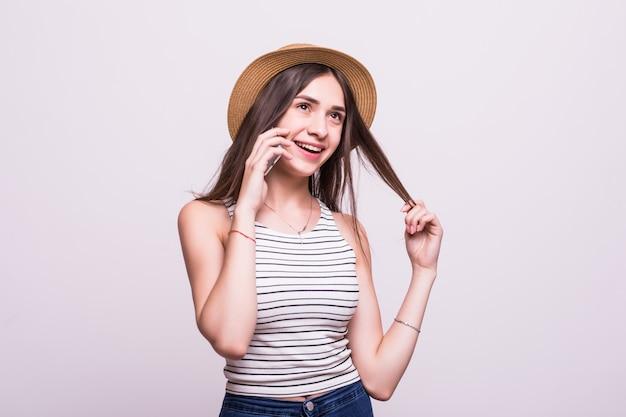 白い背景で隔離の携帯電話を使用して若い女性