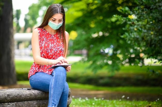 Молодая женщина с помощью цифрового планшета сидит на скамейке в парке во время коронавируса