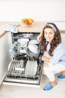 그녀의 현대적인 부엌에서 식기 세척기를 사용하는 젊은 여성.