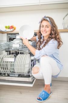 Молодая женщина, используя посудомоечную машину в своей современной кухне.