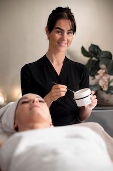 그녀의 클라이언트에 얼굴 치료를 사용 하는 젊은 여자