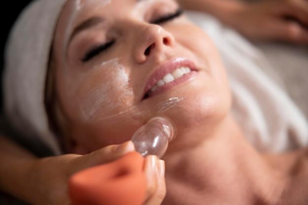 그녀의 클라이언트에 얼굴 치료를 사용 하는 젊은 여자 무료 사진