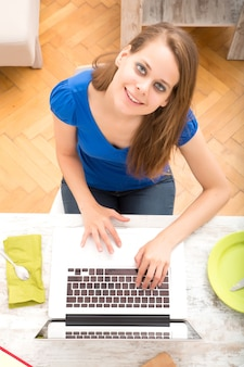朝食を食べた後、ラップトップコンピューターを使用して若い女性