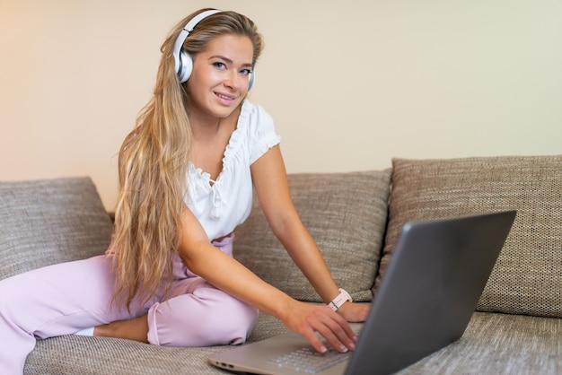 ソファでリラックスしながらノートパソコンを使用して若い女性