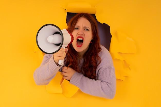 Молодая женщина использует мегафон, чтобы повысить голос через дыру в бумажной стене. концепция рекламы и продвижения.