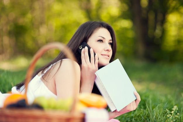 牧草地で電話を使用して若い女性