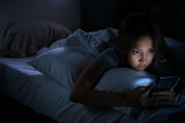 夜に彼女のベッドでスマートフォンを使用して若い女性