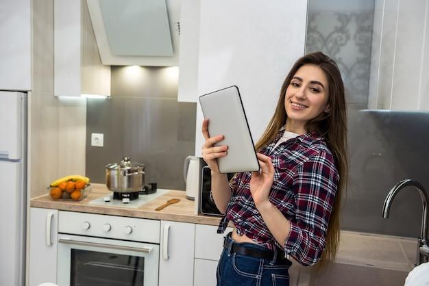 태블릿 컴퓨터를 사용하여 건강한 영양에 대한 모든 것을 그녀의 부엌에서 다른 야채를 요리하는 젊은 여성