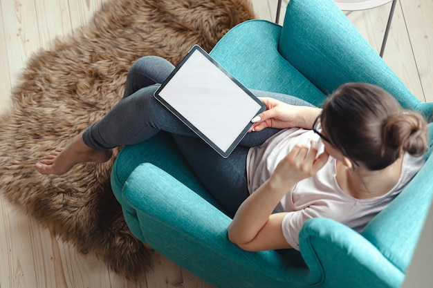 편안한 의자 평면도에 앉아 태블릿을 사용하는 젊은 여성