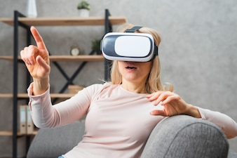Young woman using a virtual reality headset pointing her finger at something