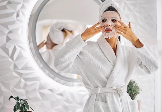Giovane donna che utilizza una maschera per il viso di bellezza