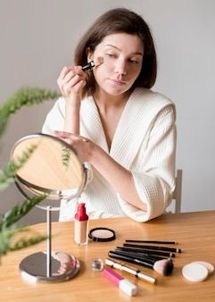 Young woman using brush for foundation