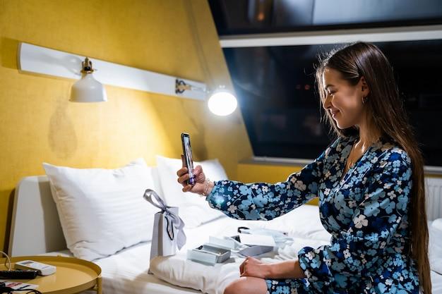 携帯スマートフォンを使用して若い女性。寝室のベッドの上の幸せな笑顔の美しい少女は、selfieを取る