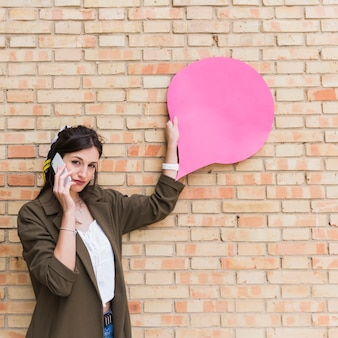 Young woman using cellphone holding pink blank speech bubble paper on brick wall