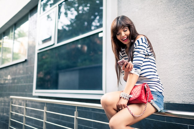 Young woman using cellphone on street.