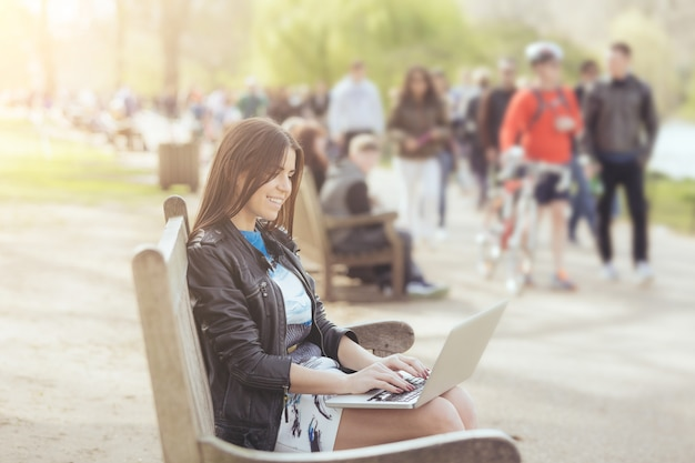 Young woman using computer at park in london
