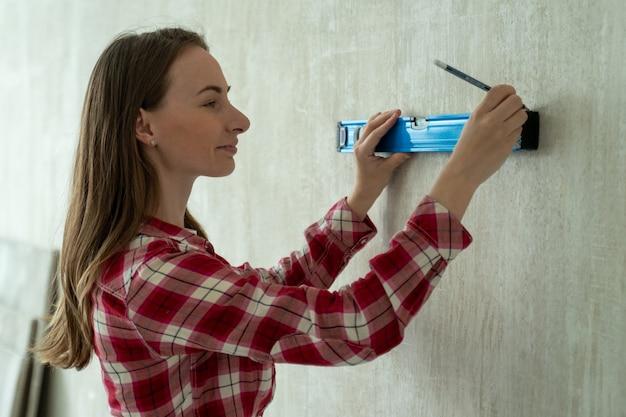 Молодая женщина с помощью строительного уровня женщина занимается ремонтом в доме