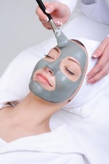 Giovane donna utilizzando la procedura cosmetica nel salone di bellezza