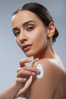 몸에 화장품을 사용하는 젊은 여성 스톡 사진