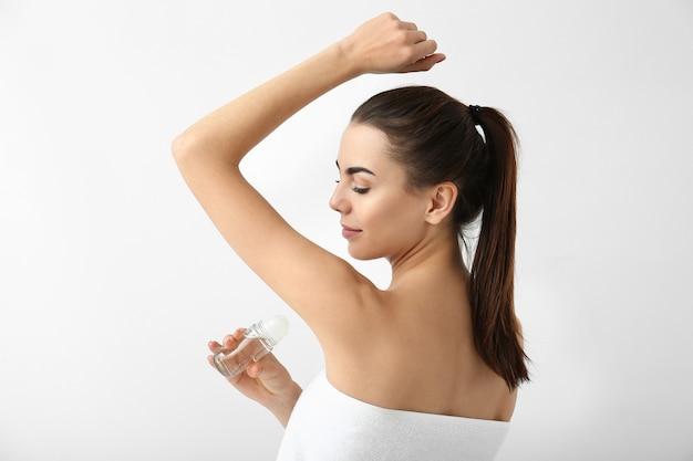 Молодая женщина с помощью дезодоранта на белом