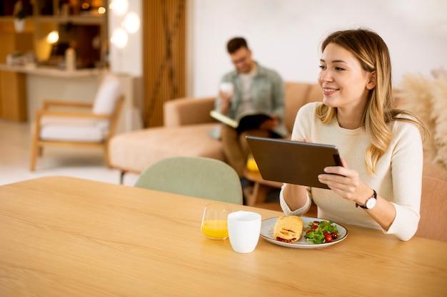 Молодая женщина, использующая цифровой планшет и завтракающая на кухне с парнем, сидящим на заднем плане