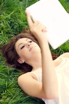 牧草地でデジタルタブレットを使用して若い女性
