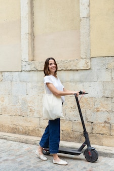 Young woman using an eco scooter