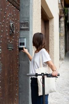 Giovane donna che utilizza uno scooter ecologico