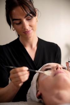 Giovane donna che usa un trattamento viso sul suo cliente