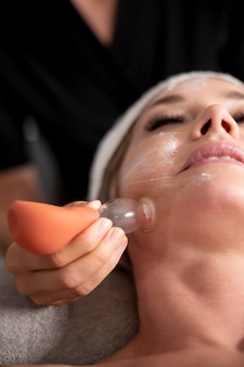 Young woman using a face treatment on her client