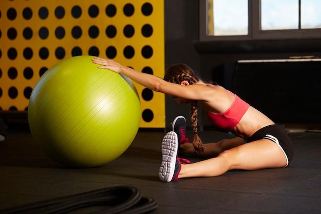 체육관에서 운동을 맞는 공을 사용하여 젊은 여자