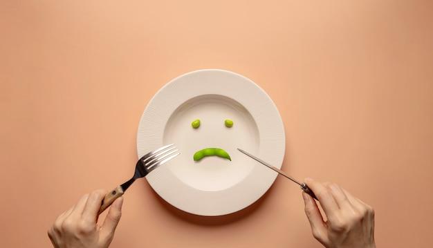 포크와 나이프를 사용하여 접시에 녹색 콩을 먹는 젊은 여자