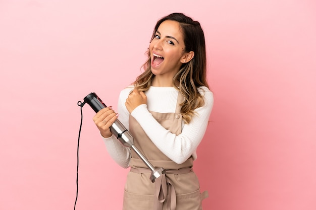 Young woman using hand blender over isolated pink background celebrating a victory