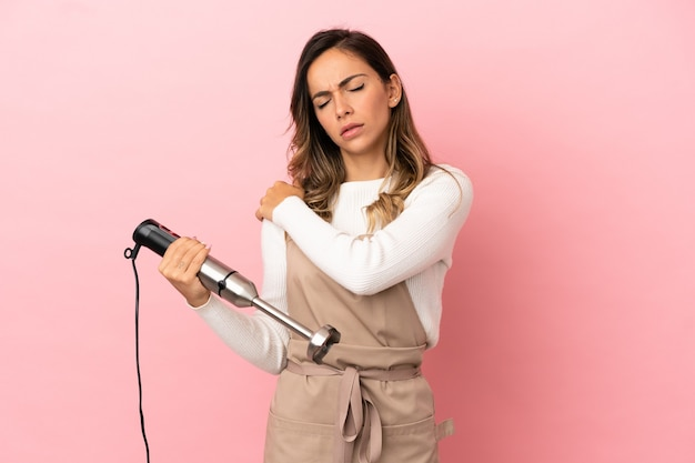 Young woman using hand blender over isolated pink background suffering from pain in shoulder for having made an effort