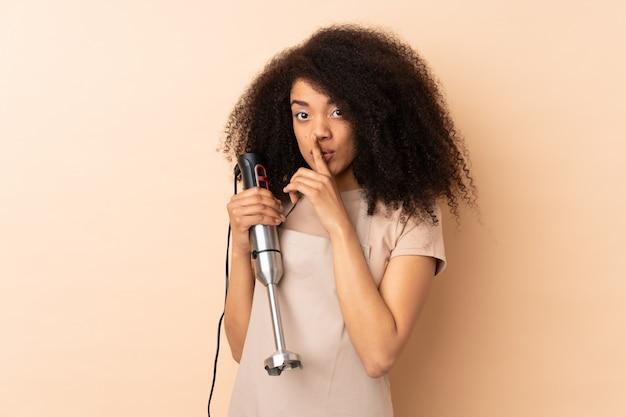 沈黙のジェスチャーをしているベージュのハンドミキサーを使用して若い女性