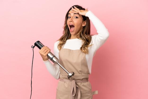 Молодая женщина, использующая ручной блендер на изолированном розовом фоне, делает неожиданный жест, глядя в сторону