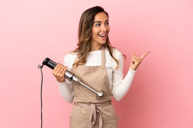 Молодая женщина использует ручной блендер на изолированном розовом фоне, намереваясь реализовать решение, подняв палец вверх
