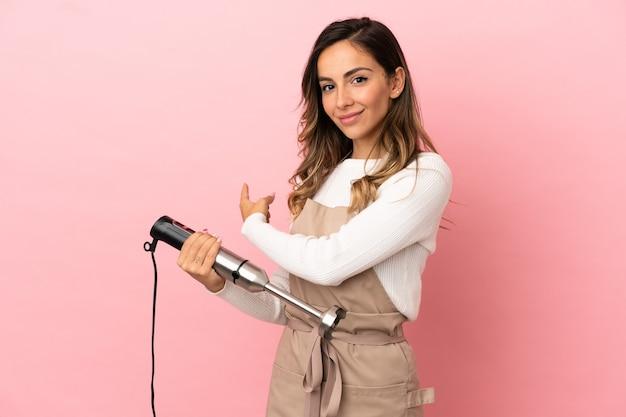 Молодая женщина, используя ручной блендер на изолированном розовом фоне, указывая назад