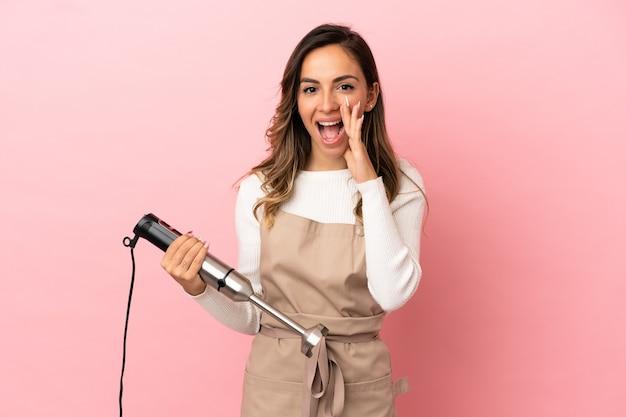 Молодая женщина, использующая ручной блендер на изолированном розовом фоне, кричит с широко открытым ртом