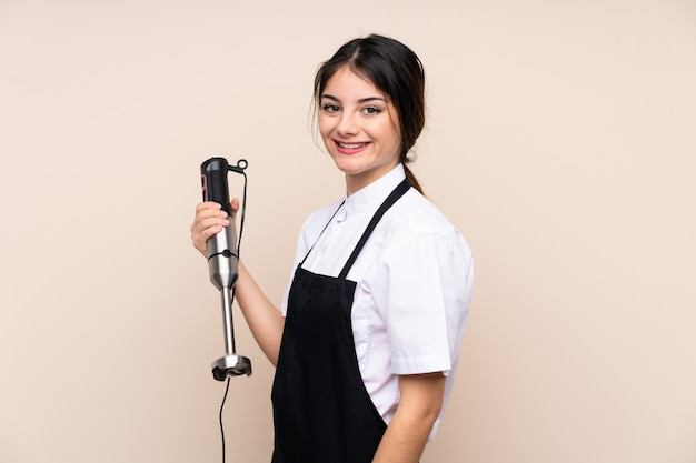 Young woman using hand blender smiling a lot