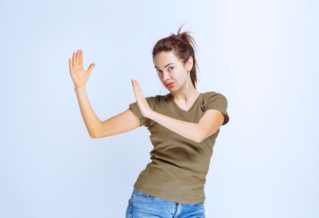 손 상단을 사용하는 젊은 여성이 무언가를 방지하고 중지합니다.